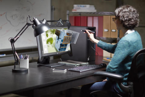 A woman works on a project using a HP Zvr 23.6 Virtual Reality Display