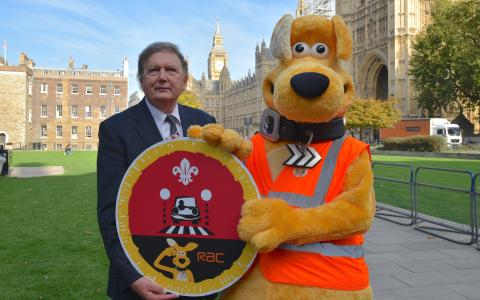 Horace and Sir Greg Knight holding Cubs Road Safety Awareness Champions badge