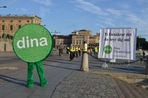 Maskot och tjänstemän från Dina Försäkringar delar ut reflexvästar till cyklister på Skeppsbron