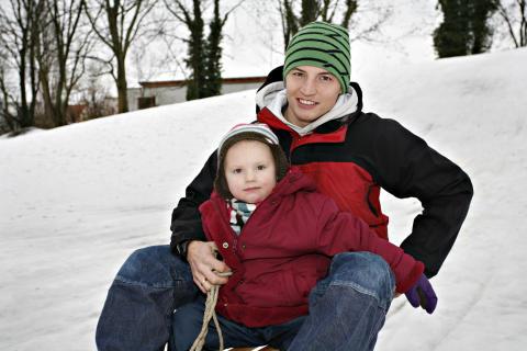 Kind mit Vater auf Schlitten