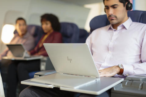 Man using a HP EliteBook x360 1030 G2 on an airplane.