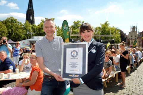 Lena Kuhlmann, Schiedsrichterin von GUINNESS WORLD RECORDS®  überreicht Tino Gottschalk, Geschäftsführer von Arla Foods Deutschland, die offizielle Urkunde.