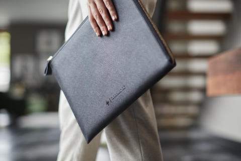 Woman holding the HP Spectre 13.3 Split Leather Sleeve