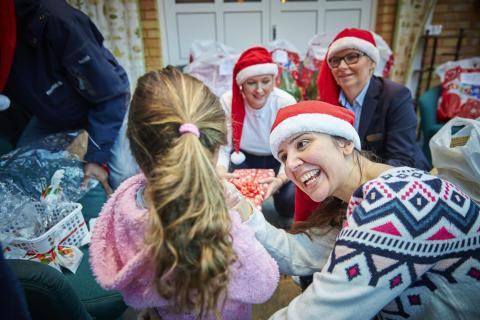 En av Mimers anställda ger en julklapp till en flicka på asylboendet