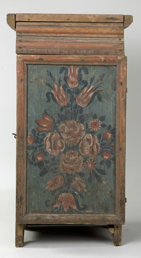 Skåp av furu, på dörrfältet blomstermålning i mörkblått och rött på blågrön botten. Inköpt från Stenvassa, Vårdsnäs socken.