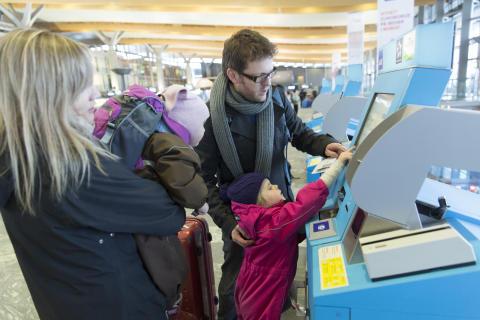 Familie ved innsjekkingsautomat