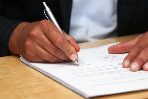 Hans Lindbäck skriver på avtalet