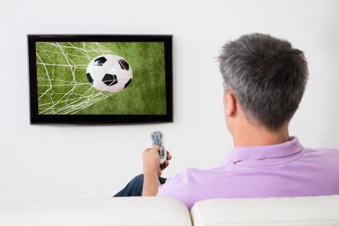 Man ser fotboll på TV