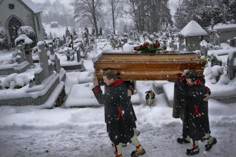 Orszak żałobników brnie poprzez mokry śnieg na bukowiańskim cmentarzu