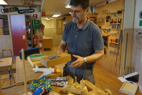 Läraren Kenneth Remnås tittar på en del av de leksaker åttorna har tillverkat utifrån förskolebarnens ritningar.