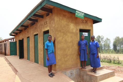 (Left to right) Valentine, 12, Selephine, 12 and Claudine, 12, standing by the girls' school latrine block, Juru Primary school, Juru Sector, Rwanda.