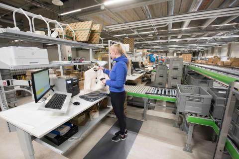 På arbejdsstationerne til e-handel samles og pakkes hængende tekstiler og øvrige produkter i forsendelseskasser.