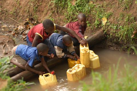 Roger (14 år) och Allen (7 år) hämtar vatten från en oskyddad vattenkälla, Buwambou Parish, Wakiso, Gombe, Uganda