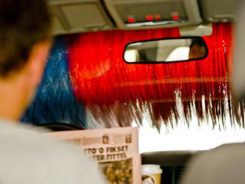 Bilvask - person læser avis i bil i vaskehal