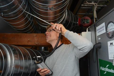 Eivind Bryne Retterstøl måler luft i kanal på loftet