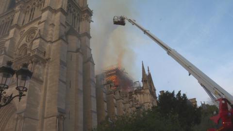 Brandmand i kran forsøger at slukke branden i Notre Dame