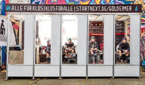Fünf Männer sitzen für 24 Stunden auf fünf Komposttoiletten