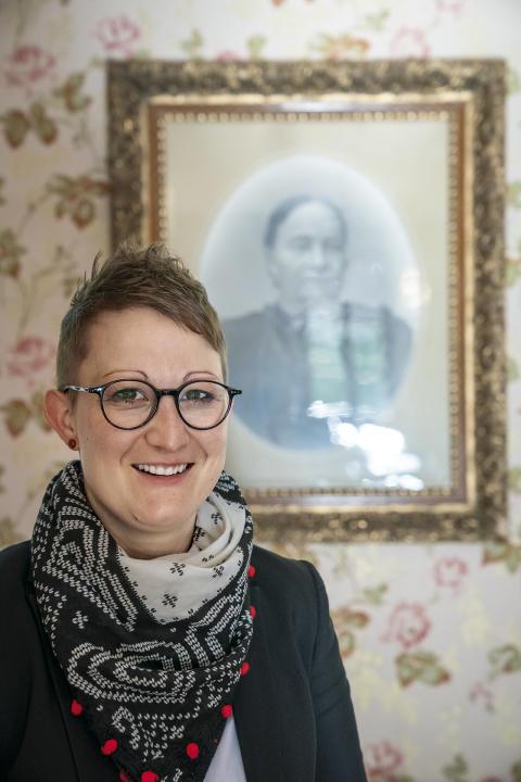 Regula Hüppi vor einem Portrait der ersten Direktorin Maria Schmid, Hotel Ofenhorn, Binn