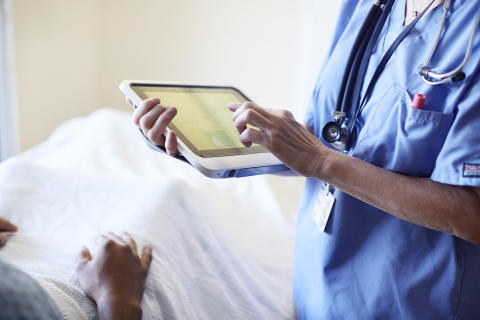 A nurse checks on a patient using a HP ElitePad with a Healthcare Jacket
