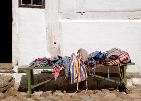 Förkläden och sjaletter på en bänk på Kulturens Östarp