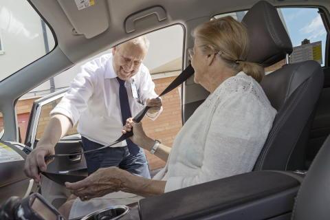 Förare hjälper kund att spänna fast säkerhetsbältet i fordonet innan färd.