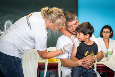En pojke från Afghanistan vaccineras i Grekland.