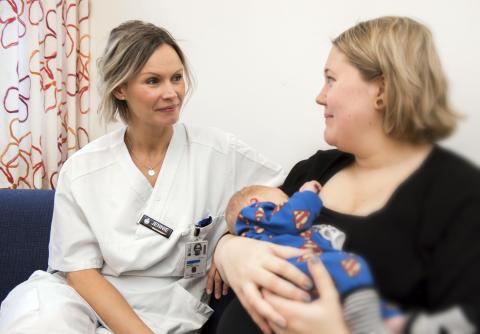 Barnmorska i samtal med nybliven mamma, på bilden syns även den nyfödda bebisen.