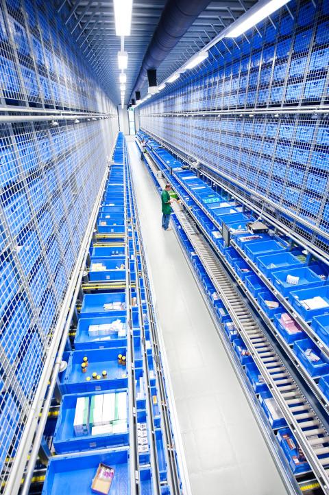 Med hjälp av de inbyggda Pick-by-Light-systemen hämtar medarbetarna de aktuella orderposterna och plockar ned dem direkt i transportbehållarna.