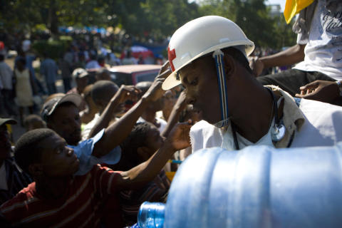 Haitiska Röda Korsets frivilliga distribuerar vatten den 15 januari 2010