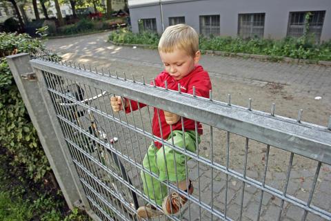Junge klettert am Gitterzaun, Querformat