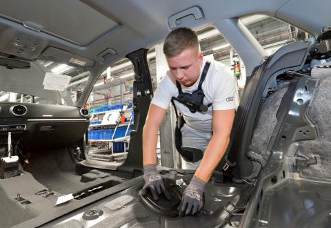 An Audi employee wears the exoskeleton to relieve the back muscles when installing the interior trim during A4 and A5 assembly at the Ingolstadt plant