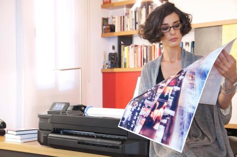 Kvinne med storformatutskrift ved HP skriver