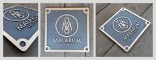 Gjutna fastighetsskyltar i brons till Mälarum fastigheter. Till ett bestånd med betoning på kulturbyggnader