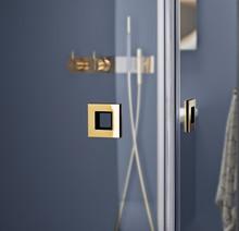 Duschväggar med mässingsdetaljer ger värme till våra nordiska badrum