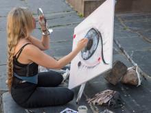 Konstnär tar plats framför Handelshögskolans huvudentré