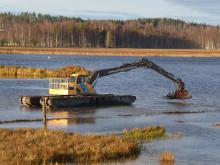 Flytande grävmaskin fortsätter att befria Limsjön i Leksand från vattenaloens grepp