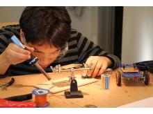 Koncentrerad kille som går kursen robotbygge hos Studiefrämjandet