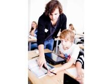 Lärarvikarie från VRE Education hjälper elev på lektion.