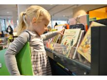 Saga letar bland böckerna på barnavdelningen på Alingsås bibliotek.