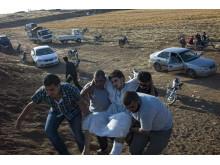 En sårad män får hjälp över gränsen till Jordanien