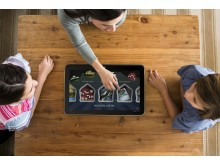 Mother and children playing a game on the HP ENVY ROVE 20 Mobile All-in-One on a coffee table (aerial view)