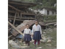 Syskon vid raserad skola i Nepal