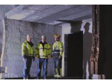 Foran inngangen til en av rømningsveiene hvor hus murt av Leca danner gasstette rom mellom løpene: Lecas representant i Bergen Sturle Stenhjem, Per Hovden Lynghaug og Implenias byggeleder Ingvar Haukelid