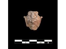 Maske-amulet med målestok.