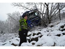 Olav Øivindson Eike står tæt ved floden med en forulykket lastbil i baggrunden