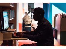 Man vid dator på Kista bibliotek