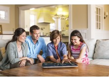Family playing a game on the HP ENVY ROVE 20 Mobile All-in-One in home living room