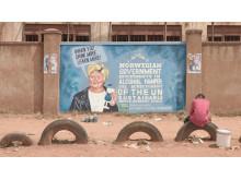 Erna Solberg på en vegg i Uganda