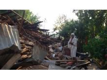 Mohan in Trauerkleidung vor den Trümmern seines Hauses