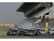 Timo Scheider i Audi tar ledningen in i första kurvan före Mercedesföraren Bernd Schneider